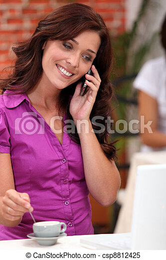 Woman on a cellphone while stirring an espresso in a restaurant - csp8812425