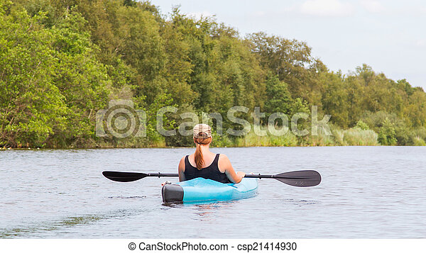 Woman on a small river in rural landscape - csp21414930