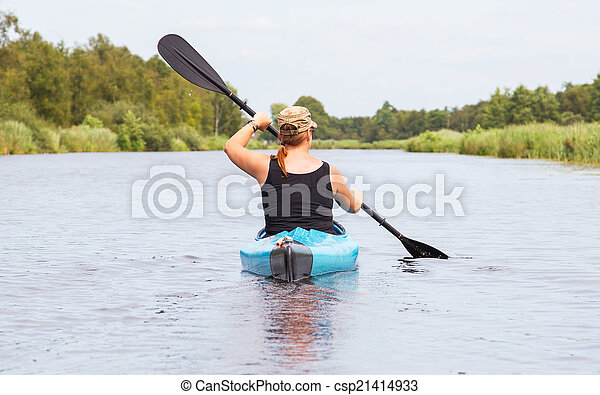 Woman on a small river in rural landscape - csp21414933