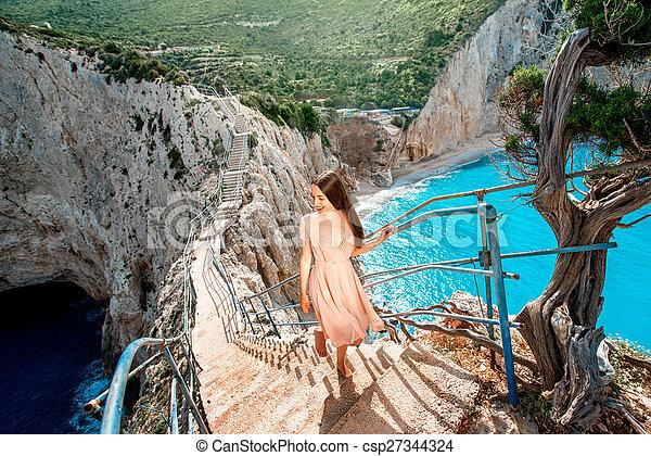 Woman on the rocky island beach - csp27344324