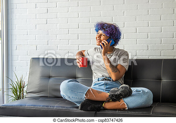 woman on the sofa at home with cup of coffee talking on mobile phone - csp83747426