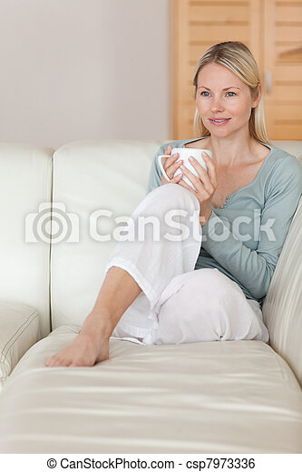 Woman on the sofa relaxing with a cup of coffee - csp7973336