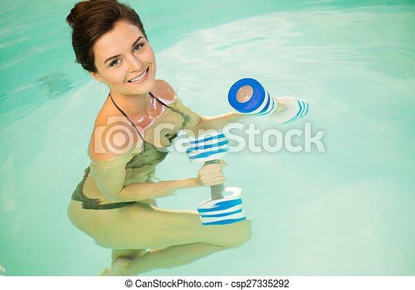 Woman on water aerobics workout - csp27335292