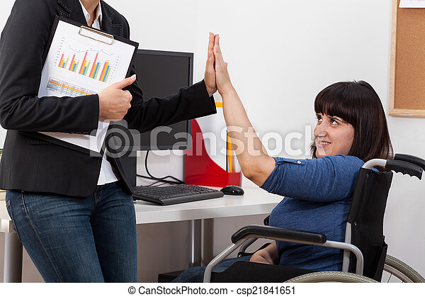 Woman on wheelchair and her co-worker - csp21841651