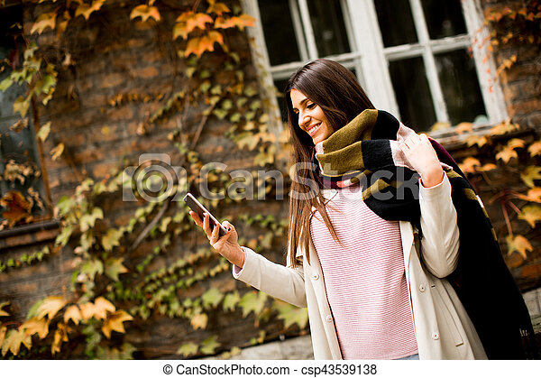 Woman outdoor with mobile phone - csp43539138