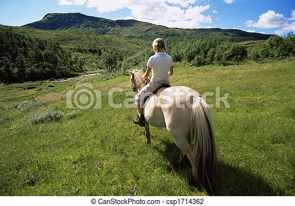 Woman outdoors riding horse in scenic location - csp1714362