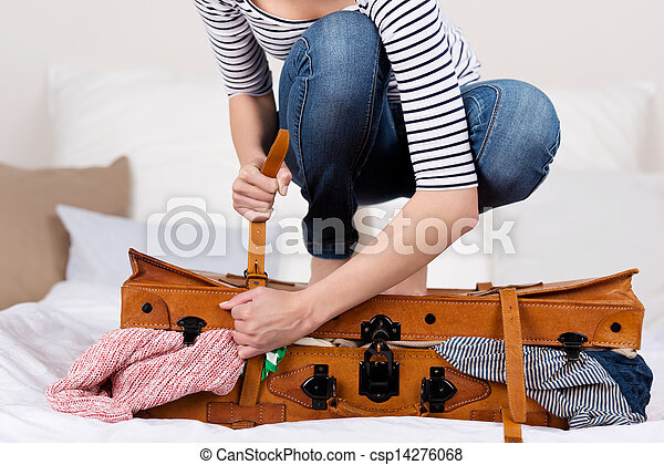 Woman Packing Suitcase On Bed - csp14276068