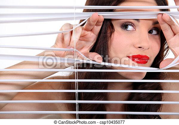 Woman peering through some blinds - csp10435077