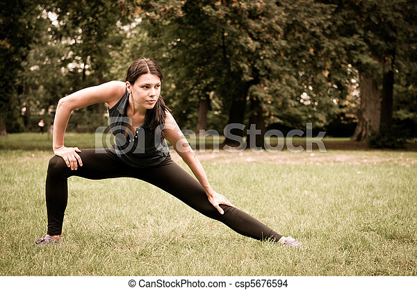 Woman performs stretching before sport in park - csp5676594