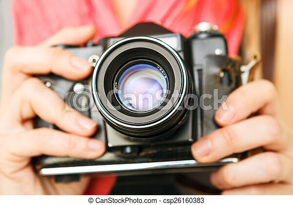 Woman photographer holding old 35mm film camera. - csp26160383