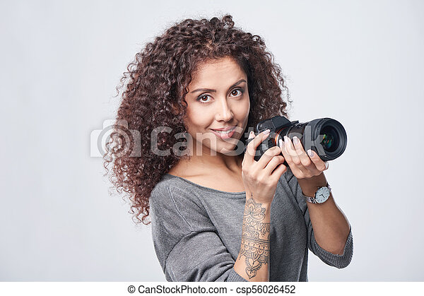 Woman photographer with professional photo camera - csp56026452