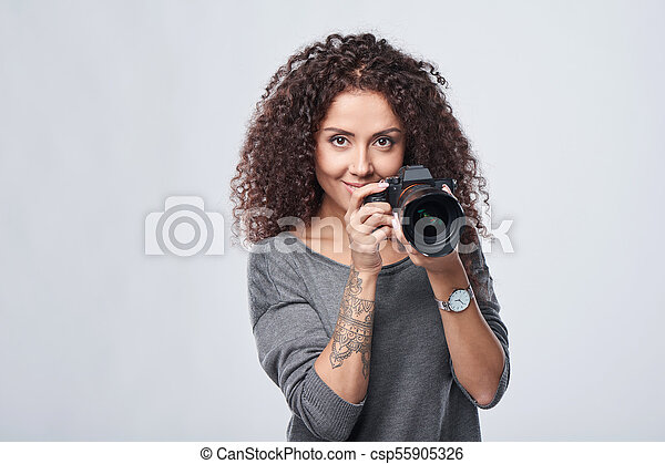 Woman photographer with professional photo camera - csp55905326