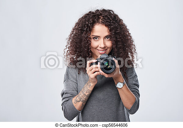Woman photographer with professional photo camera - csp56544606