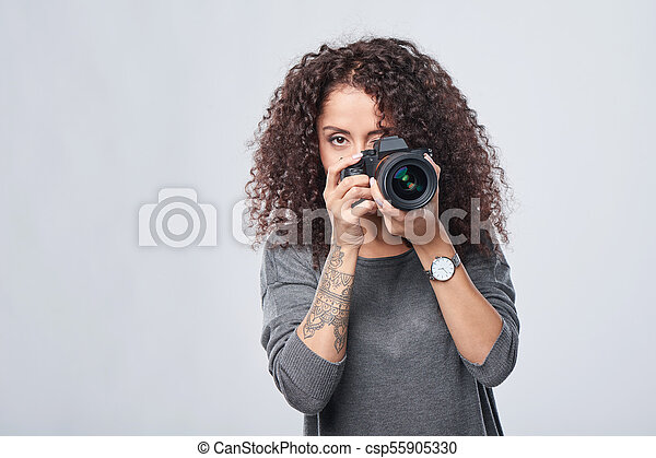 Woman photographer with professional photo camera - csp55905330