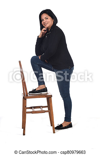 woman playing with a chair in white background, hand on chin and foot on the chair - csp80979663