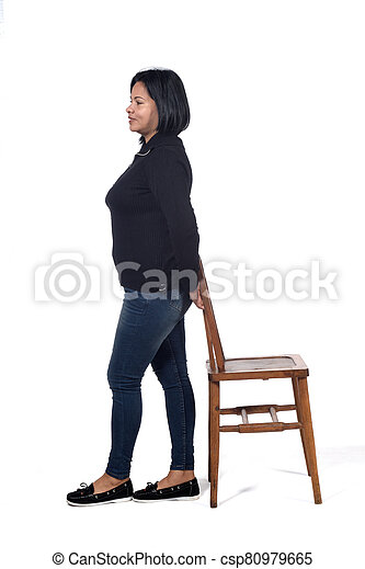 woman playing with a chair in white background, profile - csp80979665