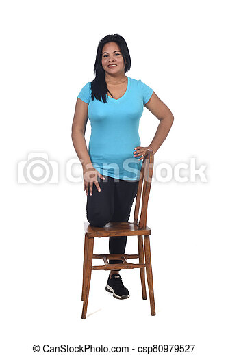 woman playing with a chair in white background, with the knee in the chair - csp80979527