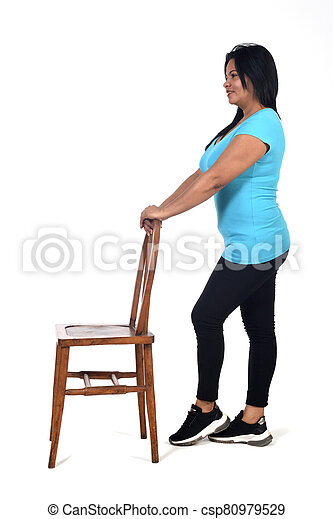 woman playing with a chair in white background, profile - csp80979529