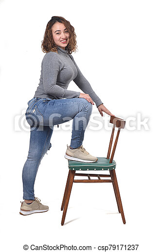 woman playing with a chair in white background - csp79171237