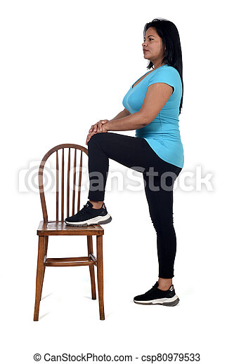 woman playing with a chair in white background, with the foot in the chair - csp80979533