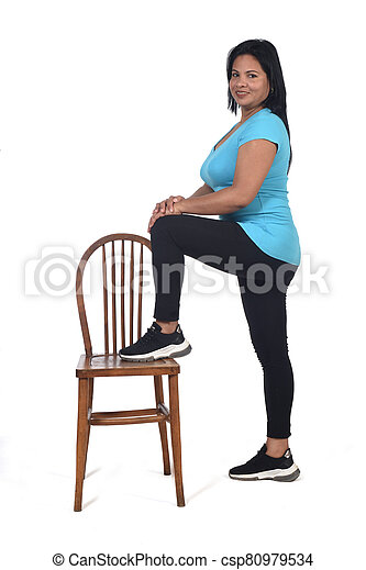 woman playing with a chair in white background, with the foot in the chair and looking at camera - csp80979534
