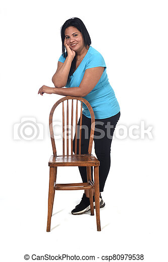 woman playing with a chair in white background, leaning on the chair - csp80979538
