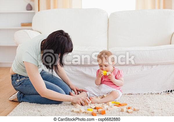 woman playing with her baby in while sitting on a carpet in the living room - csp6682880