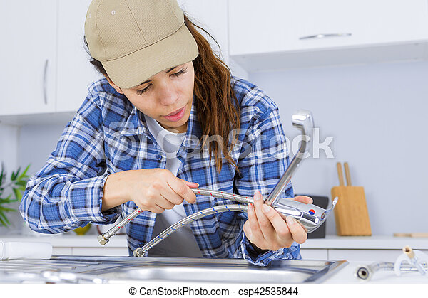 Woman plumber fixing a sink stock photo - Search Photographs and ...