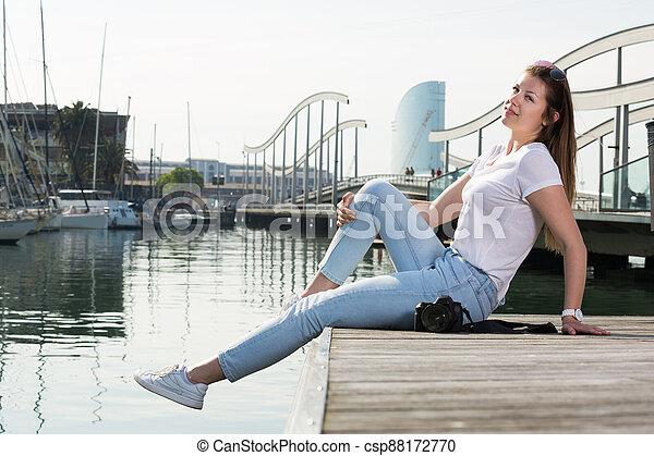 Woman posing at quay and smiling - csp88172770