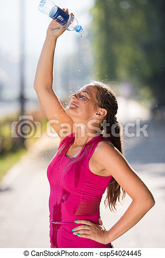 woman pouring water from bottle on her head - csp54024445