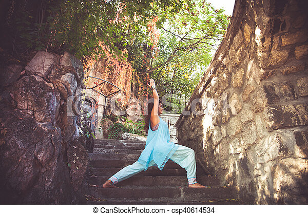 young woman practice yoga on old stairs outdoor warrior poses