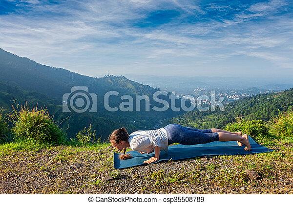 woman practices yoga asana chaturanga dandasana beautiful