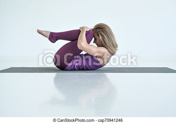 woman practicing yoga doing knees to chest exercise