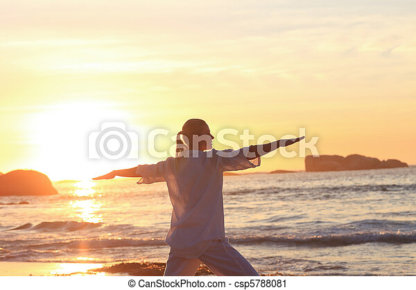 Woman practicing yoga during the sunset at the beach - csp5788081