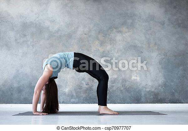 woman practicing yoga standing in urdhva dhanurasana pose