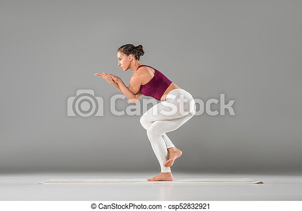 young woman practicing yoga standing in eagle exercise