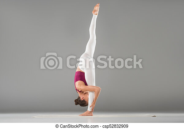 woman practicing yoga stretching in one legged downward