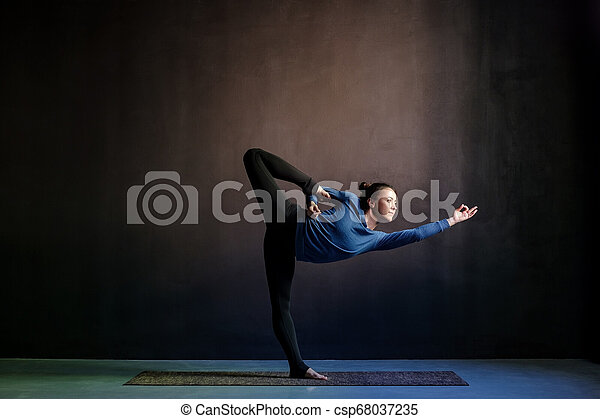 woman practicing yoga stretching in natarajasana exercise