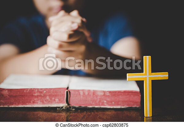 Woman praying on holy bible in the morning  Teenager woman hand with Cross  and Bible praying, Hands folded in prayer on a Holy Bible in church concept