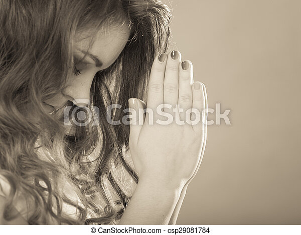 Religious woman praying to god jesus christ. Strong christian religion faith. Christianity. Sepia filter.