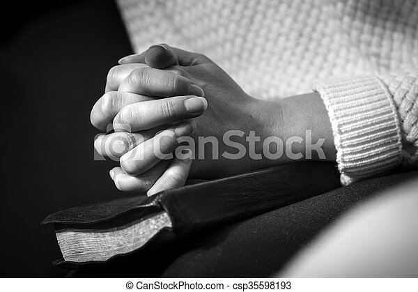 Woman prays with folded hands on the bible - csp35598193