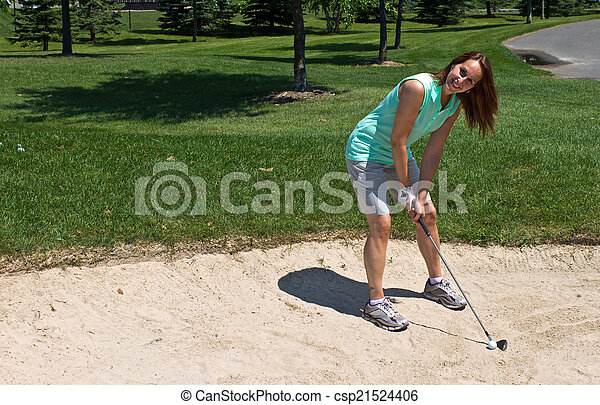 Woman prepares to swing at the golf ball caught in the sand trap - csp21524406