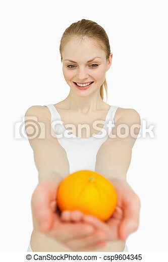 Woman presenting a tangerine while looking at it - csp9604345