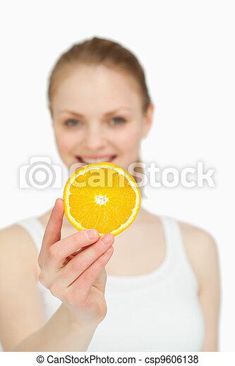 Woman presenting an orange slice while smiling - csp9606138