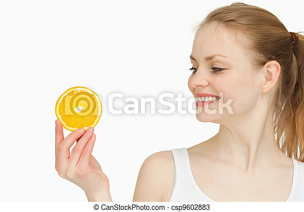 Woman presenting an orange slice while looking at it - csp9602883