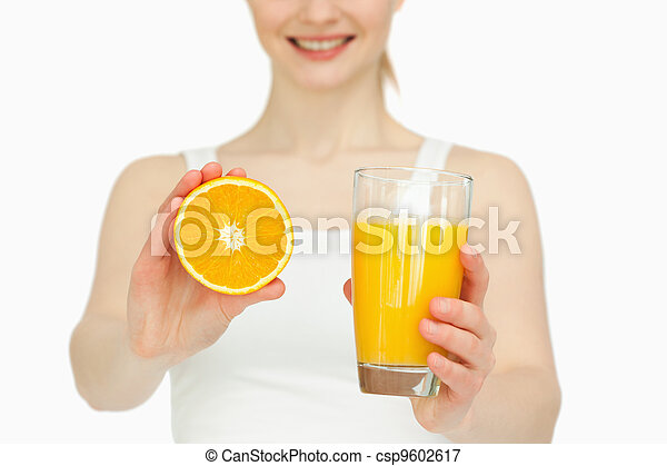 Woman presenting an orange while holding a glass - csp9602617
