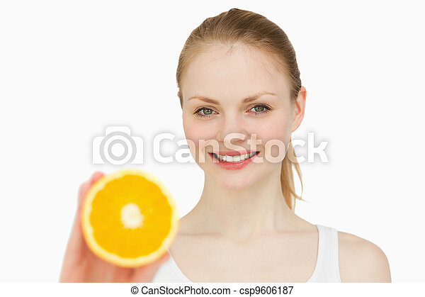 Woman presenting an orange while smiling - csp9606187