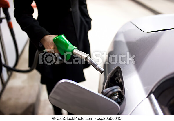 Woman pumping gas at petrol station  - csp20560045