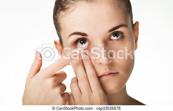 Woman putting contact lens in her eye - csp33535678