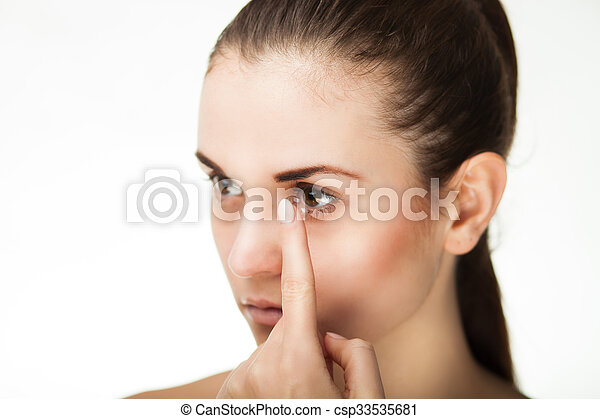 Woman putting contact lens in her eye - csp33535681